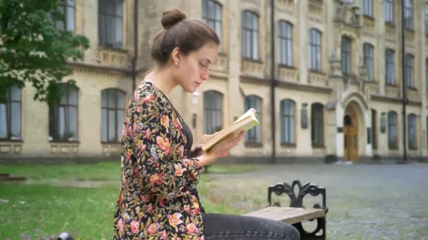 Young beautiful female college student studying, reading book and sitting on bench on street near university