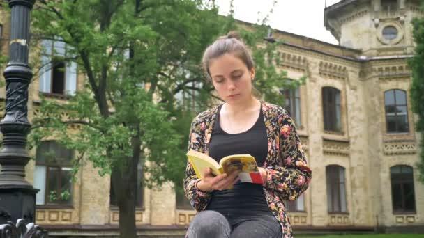 Mladí okouzlující vysokoškolský student knihu a sedí na lavičce na ulici nedaleko budovy kampusu, koncentrovaná a určeny
