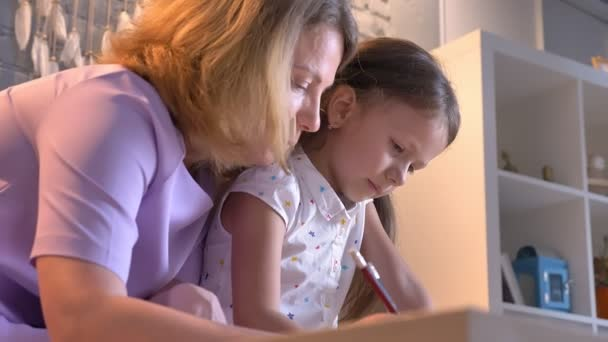 Caucasian mother doing homework with her daughter, helping kid with study, sitting at modern home, family concept indoors