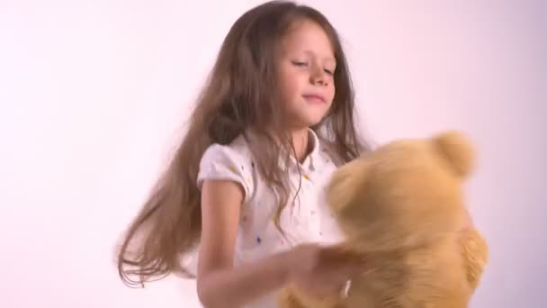 Little kid playing with plush teddy bear and dancing, holding toy, standing isolated on pink studio background