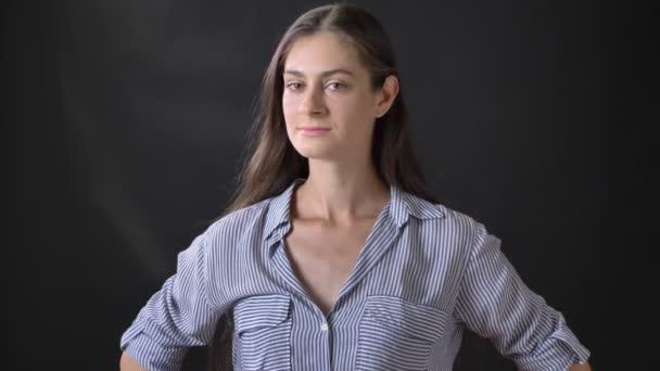 junge schöne brünette Frau im Hemd schaut in die Kamera, steht isoliert auf schwarzem Hintergrund