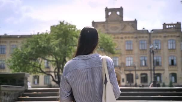 Zadní pohled na vysokoškolský student s dlouhými vlasy chůzi nahoru na univerzitu, připraven ke studiu