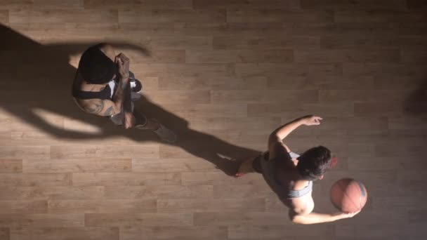 Topshot, two basketball players playing one on one on court indoors