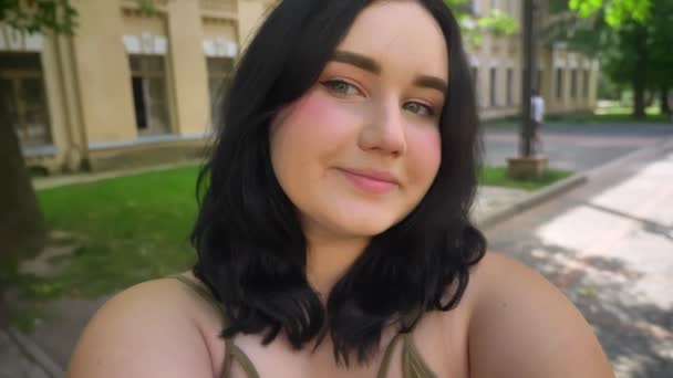 Charming young happy woman with obesity taking selfie or recording video and smiling, standing on street near college building