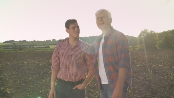 Old happy farmer showing cultivated field to his son and smiling, dad teaching his heir about agriculture, lens flare during sunset