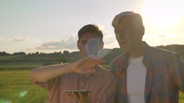 Old father with adult son discussing new project and pointing forward at wheat field, young man holding tablet, sunset in background