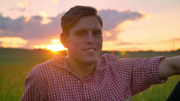 Beautiful young man smiling and looking at camera, sitting on wheat field, amazing nature with sunset in background