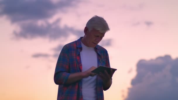 Old handsome man in short typing on tablet, pink amazing sky with clouds in background