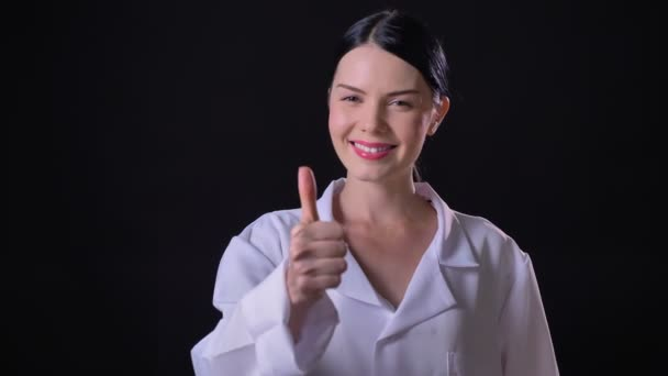 Confident young female scientist in white coat showing thumbs up into camera and smiling, isolated on black background