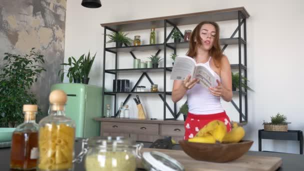 Krásná žena s nazrzlé vlasy čtení kuchařské knize fakírských i tanečních v moderní kuchyni, dobře baví doma