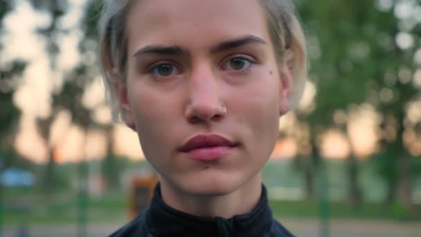 Portrét krásná blondýnka s piercingem nosem, při pohledu na fotoaparát a usmíval se, souhlasně přikyvují, park v pozadí