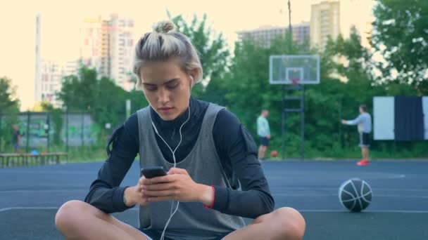 Krásná mladá žena sedí na košíkovou a psaní na telefonu, sluchátka, park s mrakodrapy v pozadí