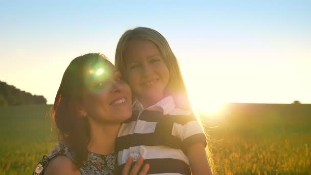 Okouzlující mladá matka objímala svou malou dcerou blondýna, při pohledu do kamery a usmívá se, pšeničné pole při západu slunce v pozadí