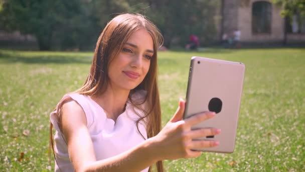 sexy Lady sitzt tagsüber auf Gras im Park, hat Videoanruf auf Tablet, Entspannungskonzept, Kommunikationskonzept