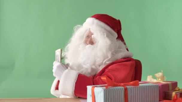 Spokojený Santa Claus drží dolarů, peníze a ukazuje znak vkus chromakey v pozadí.