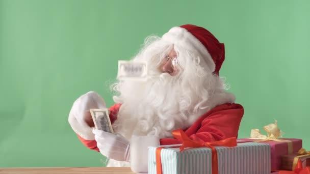 Spokojený Santa Claus házet bankovky z balíku peněz na stole, peníze na stole, chromakey v pozadí.
