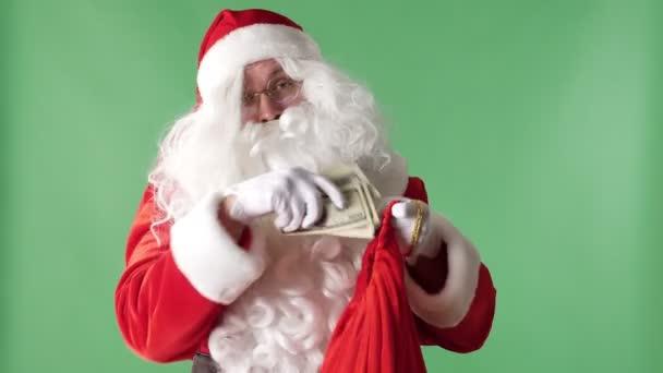 Santa Claus má hromadu účtů z červenou tašku, peníze koncept zelených chromakey v pozadí.