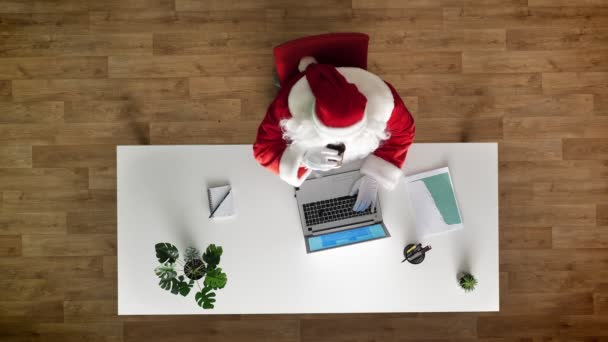 Santa Claus working at office on laptop, typing, drinking cofee, aerial view, top down shot