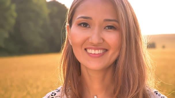 Cute asian dívka smích na pšeničná pole a těší sunlights