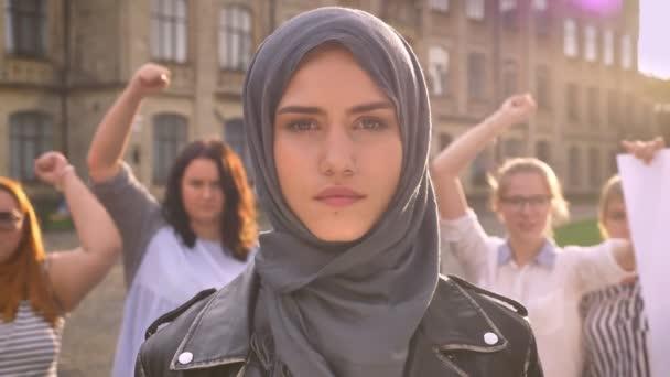 Hrdý kavkazské mladá žena v hidžábu, stojící poblíž feministky hlasování citově a demonstrovat sílu