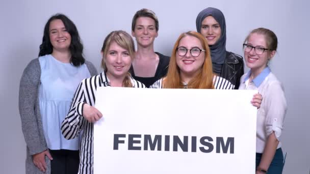 Various caucasian group of girls standing with sing feminism close to each other smiling inside