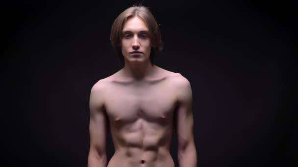 muskulöser nackter junger weißer Sportler, der mit Macht auf schwarzem Hintergrund in die Kamera blickt
