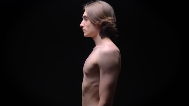 muscular caucasian man standing straight in profile naked in studio on black background