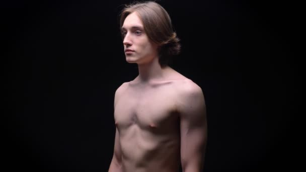 muscular strong caucasian naked boy breathing and standing calm with black background beside