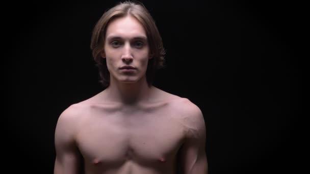 sportlicher kaukasischer Mann, der im Studio ohne Stoffvorführung in die Kamera blickt