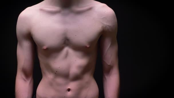 Sportos kaukázusi srác, ő abs mutatja a meztelen test, és állandó továbbra is a fekete háttér
