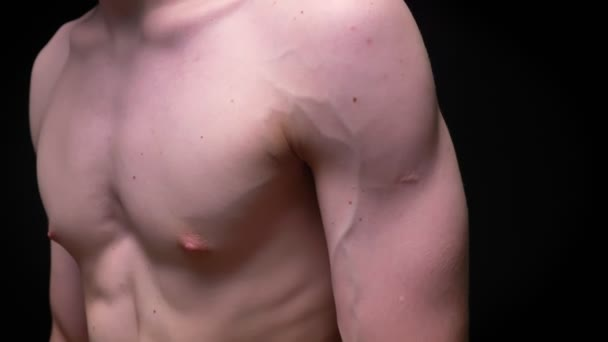 Muscular fit body and naked hands and chest of caucasian guy at the camera on black in studio