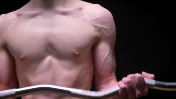 nahoře bez sportovní bílé muže s jeho svaly napjaté zvedací činka na tmavém pozadí ve studiu