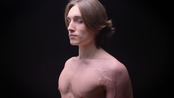 naked young caucasian boy standing in profile and looking at camera focused on black background