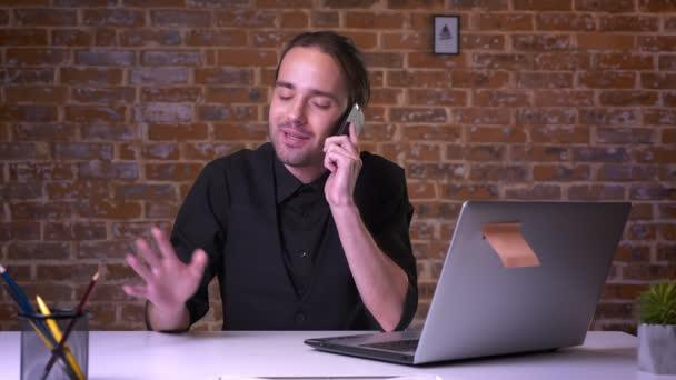 junger attraktiver Geschäftsmann telefoniert, während er im Büro mit Backsteinmauer hinter sich sitzt