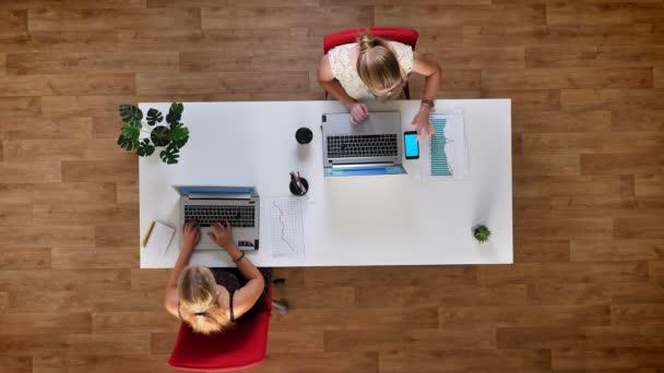 Shora dolů výstřel, dvě blondýnky pracovní, v kanceláři dřevěné, Kontrola papíru grafy s jejich obrazovek přesně, modrá obrazovka telefon leží vedle notebooku
