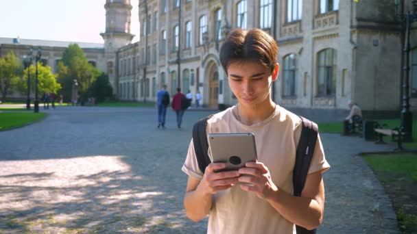 Concentrated nice asian boy is using his tablet while standing in old amazing city, spots of sunlight in, summer mood
