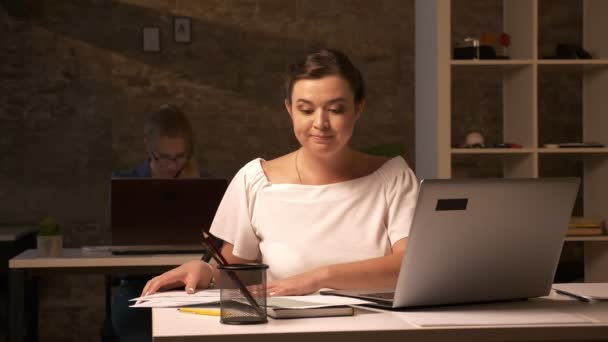 Focused thinking face on caucasian business girl who is harmonising her documents, sitting at workplace with laptop