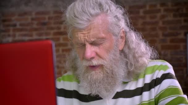 Alter süßer kaukasischer Mann arbeitet in Backstein-Büro und sitzt isoliert, brechen aus mit Laptop, seine Augen reiben und für eine Weile zu beruhigen