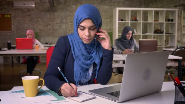 Clamly phone talk of arabaian girl in blue hijab who is sitting with colleagues behind in modern brick office and writting in notebook, diversity nowadays