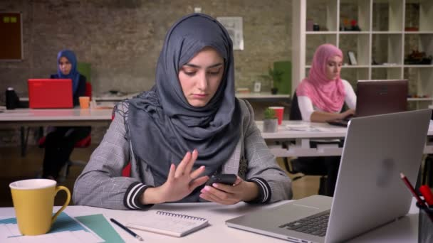 Pretty arabian female is swiping her smartphone, working atmosphere, switched on laptop, muslim girls on background ar sitting and using laptops, brick office