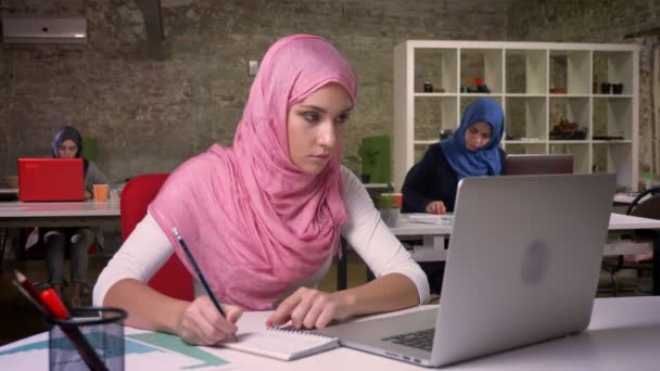 Nice working arab female in pink hijab and islamic clothes is writing down notes and looking at her laptop precisely while sitting in front of other muslim women, office vibes