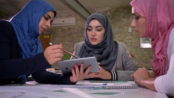 One arabic female in blue hijab is pointing to other muslim girls in  tablet, working mood, conversation with colleagues, sitting and chill,  modern office