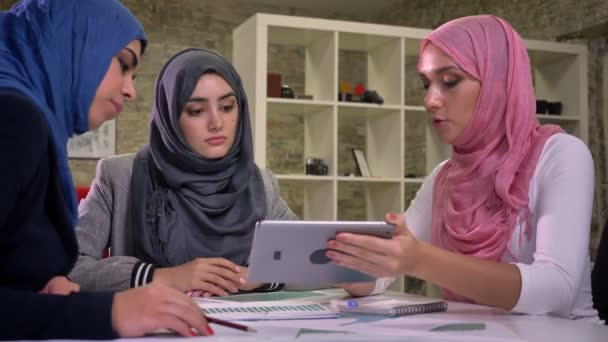 Focused sitting three arab females are holding tablet and pointing at it, working talks, notes and documents on the table, light office