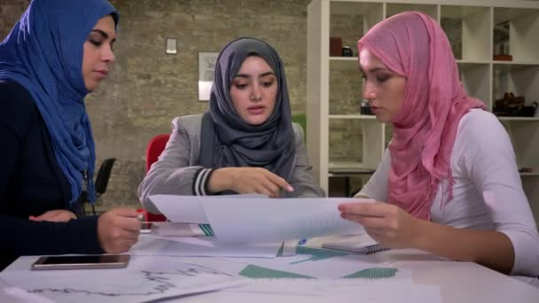 Gorgeous three arab females are sitting all together at common desktop and discussing notes and talking about work topic, middle east illustration nowadays