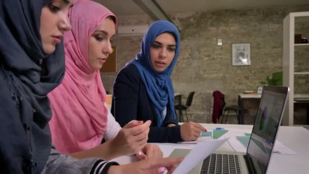 Three enjoyable hijab arabic females are sitting in line near common desktop and pointing in laptop with active discussion, inside brick office