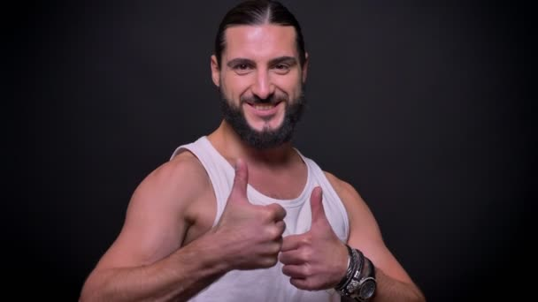 Handsome caucasian male is demonstrating like gesture with his two hands while standing isolated on black background, muscular fit body and great beard indoor