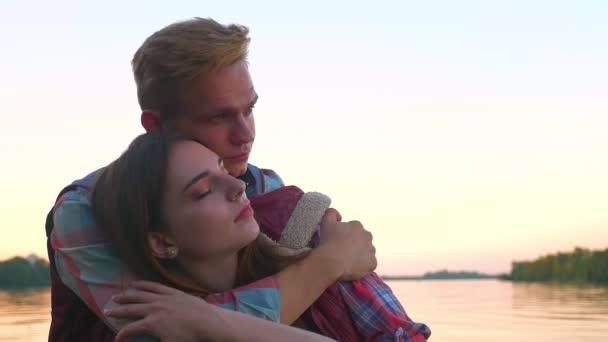Záběry muž drží jeho ženu detail, zatímco ona je relaxační s očima zavřenýma na vodní pozadí, obrázek štěstí