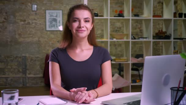 Sebevědomá žena zázvor sedí přímo na jejím pracovišti a při pohledu na fotoaparát pěkně s krásný úsměv na její uvolněný obličej, vnitřní ilustrace, pracovník