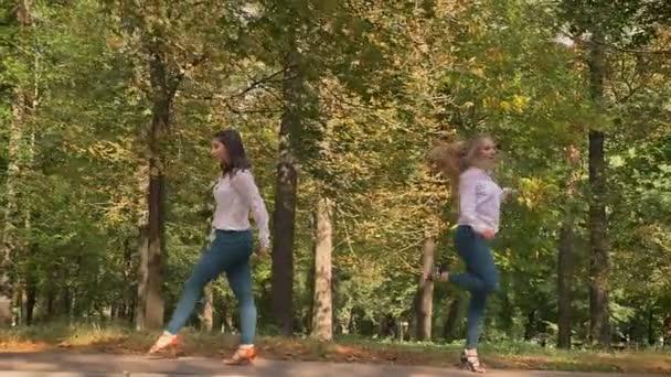 zwei schöne kaukasische Frauen tanzen und treten gemeinsam in der Natur auf, lateinischer Stil, Glück im Sommertag, Sonnenlicht, reine Schönheit, Park Hintergrund