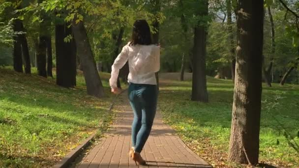 SHooting From BEhind, Beautiful Brunette Caucasian Female Is Dancing in Latin Style On Pathway In Green Park In Spring Warm Time, Pure Nature, Motions